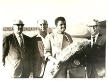 Makeba standing before an aeroplane flanked by three men