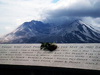 A plaque with the carved names of the eruption's victims appears, with a bouquet of flowers sitting on its center. In the background, Mount St. Helens can be seen.