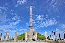 Haraldshaugen Monument is a stone column on a hill raging into the blue sky