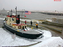 Tugboat at dockside, with three workers watching waves break over a sea wall
