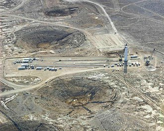 British nuclear testing in the United States - Preparing for an underground test at the Nevada Test Site. Final test preparations include running miles of cable downhole which will transmit vital test information to the diagnostic trailers to the left. A rack containing instrumentation to go downhole is assembled in the tower to the right. Subsidence craters from earlier underground tests dot the landscape.