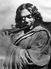 Black and white photograph of a man playing a flute