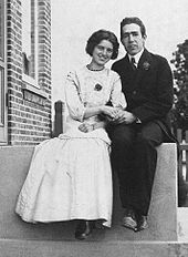 Ayoung man in a suit and tie and a young woman in a light coloured dress sit on a stoop, holding hands.