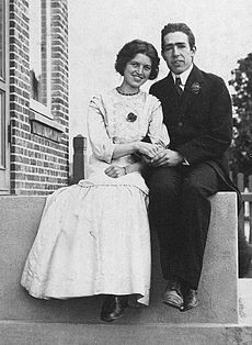 A young man in a suit and tie and a young woman in a light coloured dress sit on a stoop, holding hands