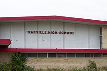 "On the side of a gymnasium, the sign reads ""Oakville High School""."