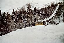 "A snow-covered ski jump with the words, ""St. Moritz"" at the base"