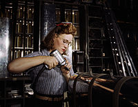 Operating a hand drill at North American Aviation, Inc, a woman is working in the control surface department assembling a section of the leading edge for the horizontal stabilizer of a plane, Inglewood, Calif.jpg