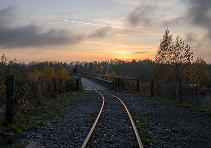 Rails of the Piesberg quarry railway and bridge, after sunset. The quarry railway (narrow gauge) is operated during summer by an association and the Museum for Industry Culture. Osnabrück, Lower Saxony, Germany