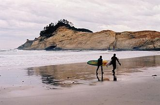 Pacific City, Oregon - Surfers in Pacific City with Cape Kiwanda in the background, November 2004