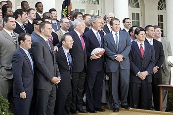 A large group of men standing together, including George Bush and Robert Kraft in the middle.