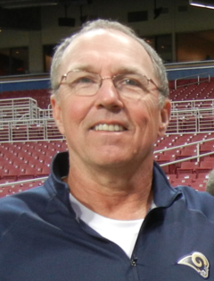 Posed head and shoulders photograph of Boudreau wearing eyeglasses and blue pullover bearing a St. Louis Rams logo standing in an apparently empty stadium