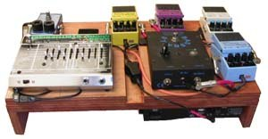 "Guitar pedalboard - Fig. 1: This picture of a custom-made wooden pedalboard shows the ""audience"" view of a pedalboard, with the pedals arrayed towards the bassist."