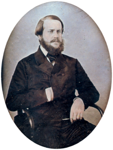 a gold-framed photographic half-length portrait of a seated bearded man dressed in a dark, double-breasted coat with his right hand tucked inside the front