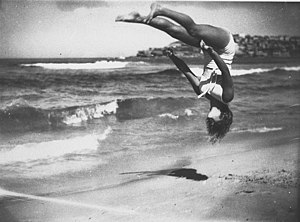 Flip (acrobatic) - Peggy Bacon is airborne while executing a variation of a back pike, with legs apart. Bondi Beach, 1937