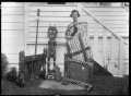 Phyllis Mary Godber wearing a Maori cloak, holding a taiaha, standing beside a collection of Maori carvings, including two fire-screens, carved by her father Albert Percy Godber ATLIB 324463.png