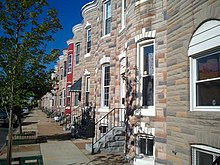 View of swell-front rowhouses with formstone.