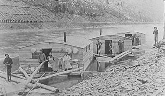 Colton Point State Park - Pine Creek lumber drive, with arks for kitchen and dining (left), sleeping (center), and horses (right): the railroad is on the shore behind.