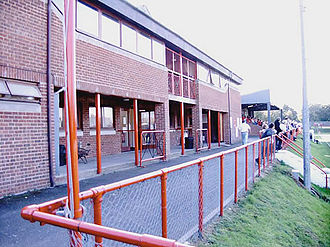 Andover F.C. -  Photograph of the Portway Stadium, showing the clubhouse, stand and banking