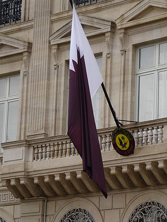 Emblem of Qatar - Flag and emblem of Qatar, displayed above the entrance of the Qatari Embassy in Paris.