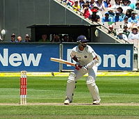 An Indian cricketer in a blue helmet, waiting to receive a delivery. He is standing in front of his wicket, with spectators in a stand behind him.