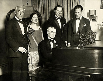 Birthday party honoring French pianist Maurice Ravel in 1928. From left to right: conductor Oskar Fried, singer Eva Gauthier, Ravel (at piano), composer-conductor Manoah Leide-Tedesco, and composer George Gershwin. Ravel Gershwin Leide-Tedesco002.jpg
