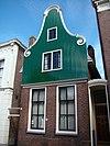 foto van Huis met houten klokgevel boven een pui van baksteen