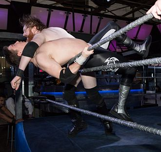 Professional wrestling attacks - Josh Rogen clotheslines Eric Cairnie over the top rope and out of the ring.