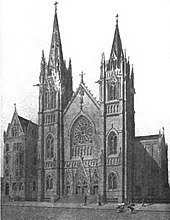 Black-and-white rendering of the front, and part of the side, of a tall, fancy church, and a 5-story parish house next door. The light is from upper left, casting shadows to lower right. There are a few figures on the sidewalk in front of the church, and an open motorcar parked at lower right.