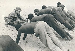Rhodesia - A soldier interrogates Rhodesian villagers in late 1977.