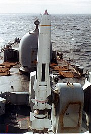 A large white missile sits on its launcher at the front of a warship.
