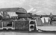 Illustrated section showing below ground structures of a riverside embankment including a covered railway line with steam train, riverside wall with sewer and pipes running behind. A large, glass roofed railway station sits in the left middle distance adjoining a railway bridge that crosses the river. Boats ply the water and tiny figures are engaged in construction work with a raised scaffold in the centre.