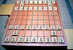A traditional shōgi-ban (shogi board) displaying a set of koma (pieces). The pieces on the far side are turned to show their promoted values. The stands on either side are komadai used to hold captured pieces. The board itself is raised for the comfort of players seated on tatami mats (background), and is hollowed underneath to produce a pleasing sound when the pieces are moved.