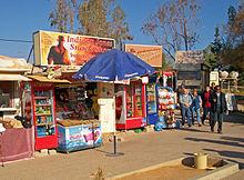 Duas pequenas lojas que oferecem produtos Coca-Cola e outros refrigerantes em contêineres refrigerados com portas de vidro.  No meio é um guarda-chuva com o logotipo da Pepsi.  Acima deles são sinais que fazem referência Indiana Jones e retratando-lo.  Um pequeno grupo de pessoas está andando passado e na frente deles à direita