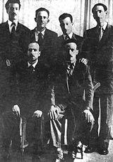 « Groupe des six », chefs du FLN. Photo prise juste avant le déclenchement des hostilités le 1er novembre 1954. Debout, de gauche à droite : Rabah Bitat, Mostefa Ben Boulaïd, Didouche Mourad et Mohamed Boudiaf.Assis : Krim Belkacem à gauche, et Larbi Ben M Hidi à droite.
