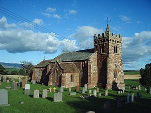 Grade I listed churches in Cumbria - A red stone church seen from the northwest with a north transept and a west tower surmounted by a battlemented parapet with machicolations and a short spire