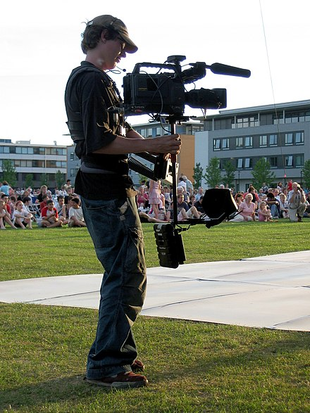 A balanced Steadicam avoids shakiness. It is not directly hand-held.