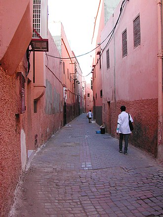 """Fused grid - A street in the Medina of Marrakech, showing the """"wall"""" effect of agglutinated buildings and the absence of lower floor windows."""
