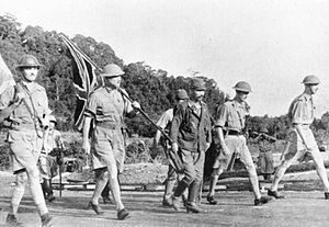 8th Division (Australia) - Lieutenant General Arthur Percival, led by a Japanese officer, walks under a flag of truce to negotiate the capitulation of Allied forces in Singapore, on 15 February 1942.