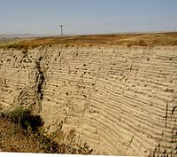 This photo shows another canyon cut into the surrounding flat soil with about 30 distinct horizontal layers of sediment, each clearly demarked from the layer below. Above the canyon a telephone pole can be seen in the distance – the pole provides the perspective that helps the viewer establish that the cut is 30–40 ft (9.1–12.2 m) deep. In the foreground one observes the near edge of the canyon, which help one establish that the canyon is quite narrow and steep walled.