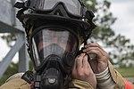 Trevette Kuester, Joint Base Andrews Fire Explorer Academy cadet, tightens his helmet straps.jpg