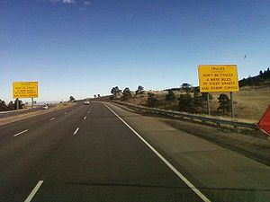 "Interstate 70 in Colorado - Warning sign stating, ""Trucks, Don't be Fooled—4 more miles of steep grades and sharp curves."""