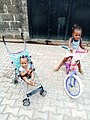 Two sisters ride on their bike and baby stroller respectively on a late afternoon.jpg