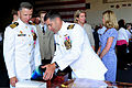 U.S. Navy Capt. Michael McKenna, right, the executive officer of the aircraft carrier USS Ronald Reagan (CVN 76), presents Capt. Thom Burke with a gift following the ship's change of command ceremony aboard 130813-N-HT107-265.jpg