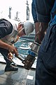 U.S. Navy Senior Chief Machinist's Mate Leonardo Josef uses a wrench to prepare a hose for the transfer of potable water during an underway replenishment aboard the guided missile destroyer USS Stockdale 130727-N-HN991-015.jpg
