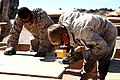 U. S. Marine Cpl. Calab Ray with Engineer Company, Combat Logistics Regiment 2, 2nd Marine Logistics Group, builds a sub-floor for a south west asia hut at their forward operations base during Enhanced Mojave 120910-M-KS710-010.jpg
