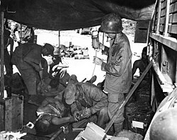 Medics treat a pair of injured men in a tent in the middle of a jungle