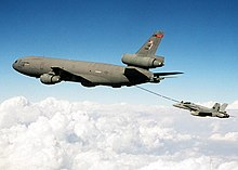 A jet aircraft refuels from a gray three-engine tanker via a long boom located under the tanker's aft fuselage.