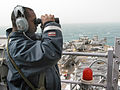 US Navy 030326-N-9122P-001 Boatswain's Mate 3rd Class Christopher Haywood searches for surface contacts while standing the forward lookout watch aboard the amphibious assault ship USS Tarawa (LHA 1).jpg