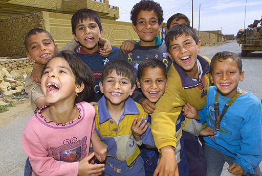 US Navy 030412-A-9330B-093 A group of Iraqi children pose for a photo while their parents receive humanitarian daily rations (HDR's) and water in the town of Ar Rutba