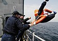 US Navy 060406-N-2385R-215 Boatswain's Mates 2nd Class John George, left, and Corey S. Masterson, right, throw a man overboard simulation device into the water.jpg
